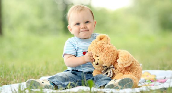 Happy baby with bear on blanket