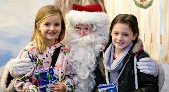 Father Christmas with 2 young girls and presents