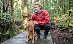 Redhead teenaged boy with Vizsla Dog resting on forest boardwalk