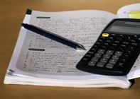 Photograph of a notebook with a pen and calculator resting on it