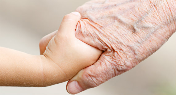 An older person holding hands with a child